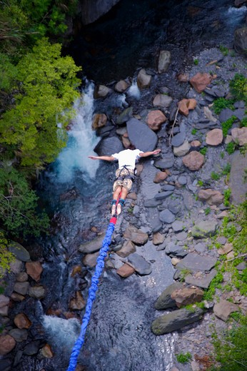 Stock Photo: 1397R-71436 Rear view of male bungee jumper falling with arms outstretched