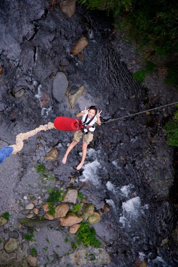 Woman bungee jumping over a stream, giving peace sign : Stock Photo