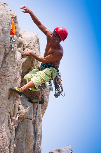 Stock Photo: 1397R-71477 Man rock climbing on cliffs