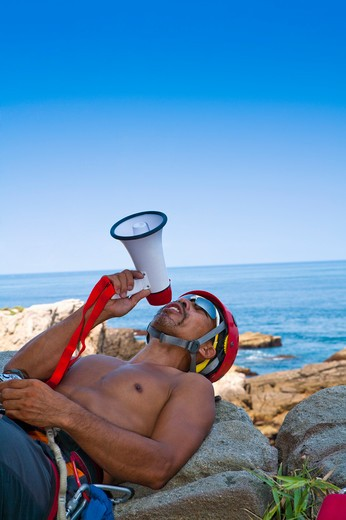 Stock Photo: 1397R-71519 Male rock climber lying on rocks and talking through megaphone