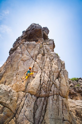 Stock Photo: 1397R-71533 Woman rock climbing on cliffs