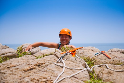 Stock Photo: 1397R-71539 Female rock climber arriving at the top of cliff, smiling