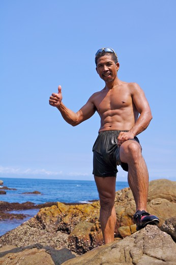 Stock Photo: 1397R-71694 Mature man standing on the rock with thumbs up, Rock Climbing, Extreme Sports