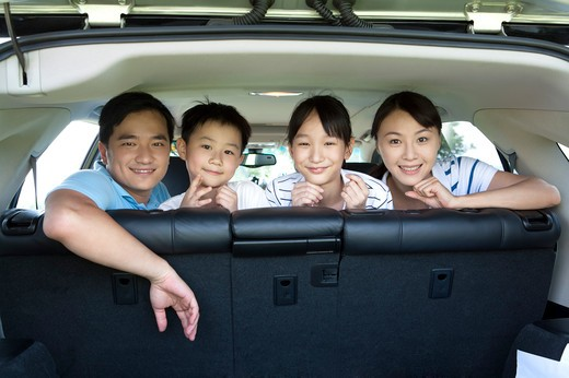 Stock Photo: 1397R-71747 Family sitting in back of car looking out back door, smiling