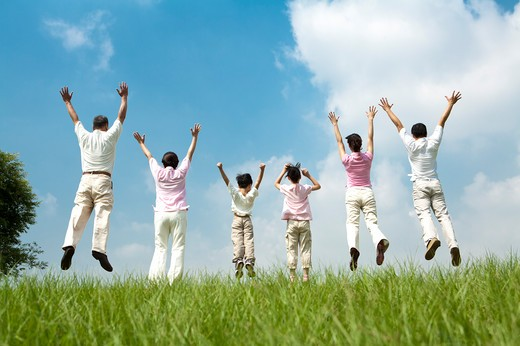 Multi-generational family jumping in a row on lawn, arms up : Stock Photo