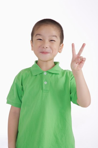 Stock Photo: 1397R-71887 Boy looking away and smiling with two fingers