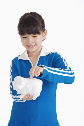 Stock Photo: 1397R-71894 Girl holding piggy bank and looking down with smile