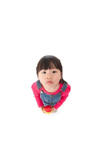 Little girl holding a small ball and looking up to camera : Stock Photo