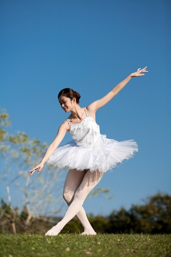 Stock Photo: 1397R-72029 Ballet dancer dancing on the lawn and looking down