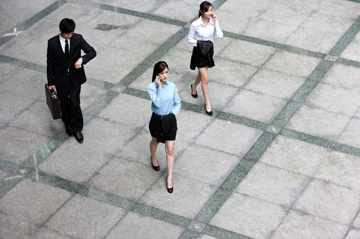 Stock Photo: 1397R-72178 Business team walking in a hurry and talking on the phone, elevated view