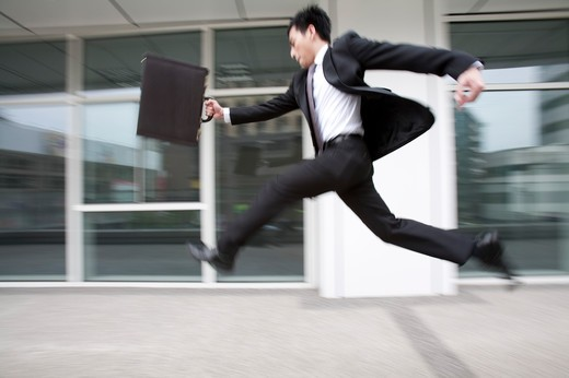 Businessman running and leaping in mid air, blurred motion : Stock Photo