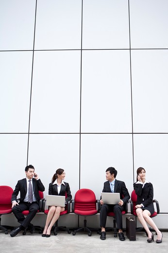 Stock Photo: 1397R-72231 Business people sitting in office chairs in a row busy with their work