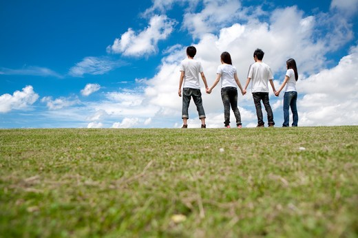 Young adults standing on the lawn and holding hands together : Stock Photo
