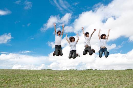Young adults jumping in mid-air together : Stock Photo