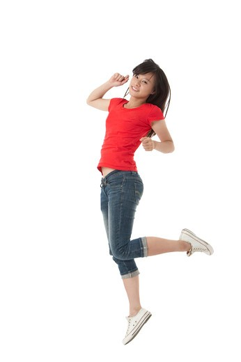 Stock Photo: 1397R-72518 Young woman jumping in mid-air with smile