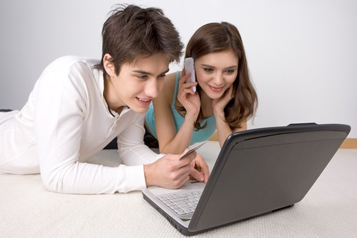 Stock Photo: 1397R-75332 Young couple paying bills on line with credit card