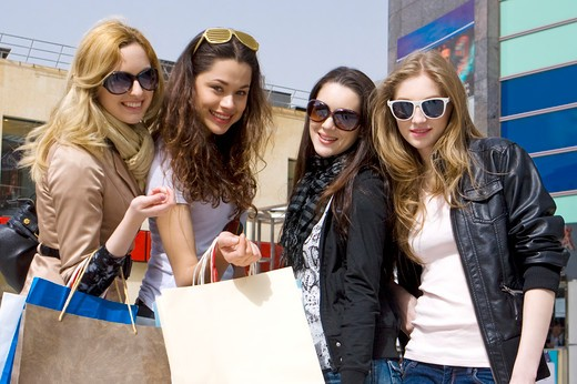 Four young women standing together and holding shopping bags, Shopping : Stock Photo