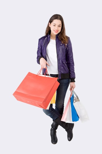 Stock Photo: 1397R-75391 Young woman standing with shopping bags and smiling at the camera, Shopping