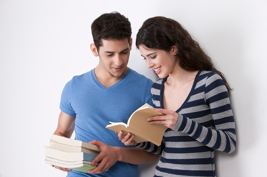 Stock Photo: 1397R-75474 Young couple reading books, smiling