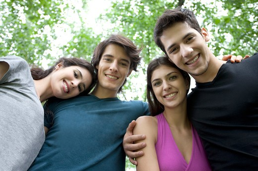 Four young friends arm in arm smiling : Stock Photo