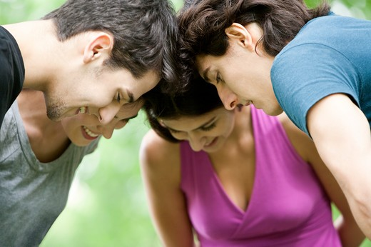 Stock Photo: 1397R-75500 Four young friends putting heads together, looking down