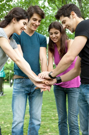 Stock Photo: 1397R-75526 Four young friends overlapping hands in a park