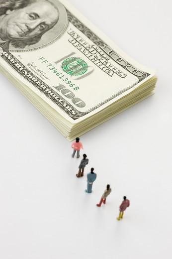 Stock Photo: 1397R-75963 Figurines waiting in line before a stack of US hundred dollar bills
