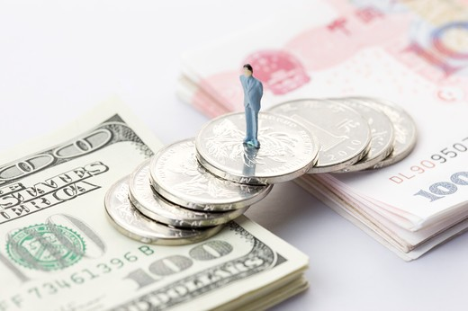 Stock Photo: 1397R-75967 A figurine standing on a bridge made of coins across two stacks of Paper Currency, one side of US Dollars and the other side China Currency