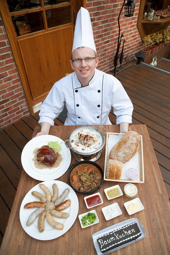 Chef with various kinds of German food, elevated view : Stock Photo