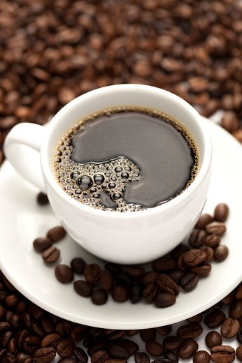 Close-up of a cup of coffee and coffee beans in background : Stock Photo