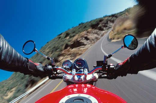 Stock Photo: 1400-455 Close-up of a person's hands on a motorcycle's handlebars
