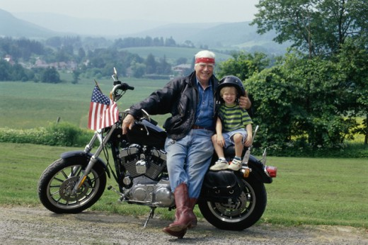 Portrait of a grandfather sitting on a motorcycle with his grandson : Stock Photo
