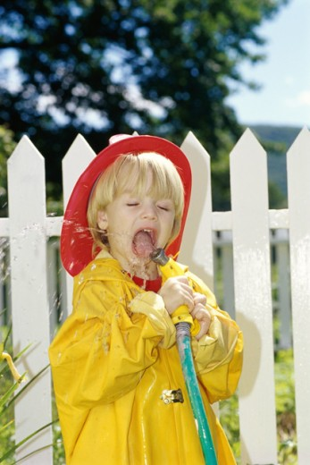 Stock Photo: 1406R-213A Boy playing with a garden hose
