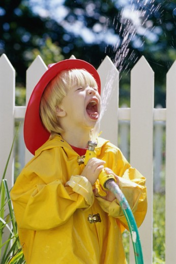 Stock Photo: 1406R-214 Boy playing with a garden hose