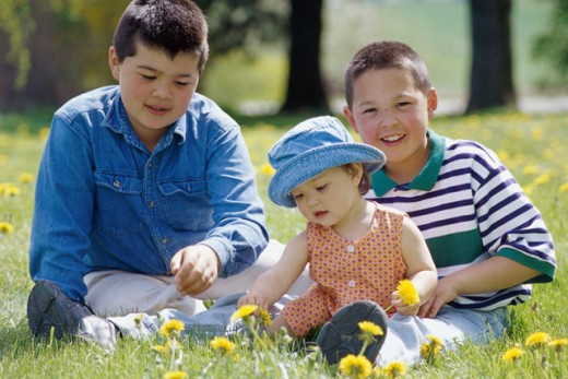 Portrait of two boys and a girl sitting on a lawn : Stock Photo