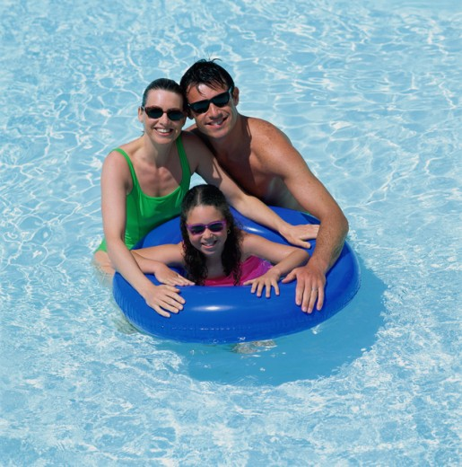 Stock Photo: 1417R-102 Father and mother with their daughter in a swimming pool