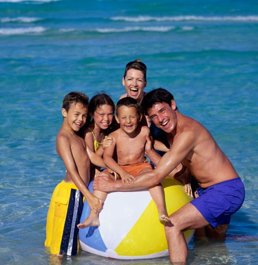 Father and mother with their daughter and sons at the beach : Stock Photo
