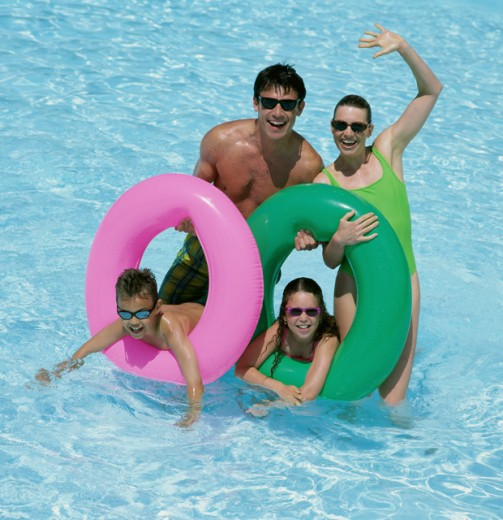 Stock Photo: 1417R-113 Father and mother with their daughter and son in a swimming pool