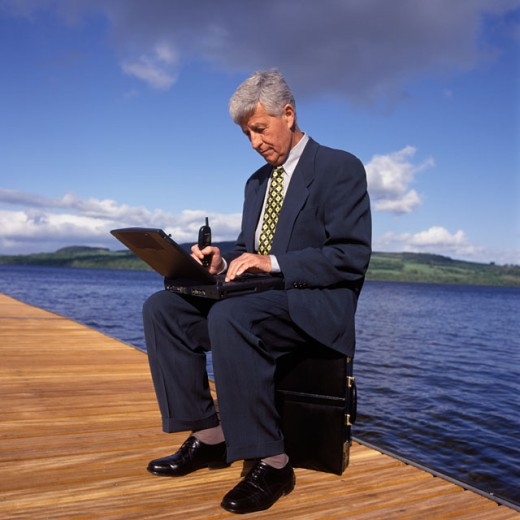 Side profile of a businessman sitting on a pier working on a laptop : Stock Photo