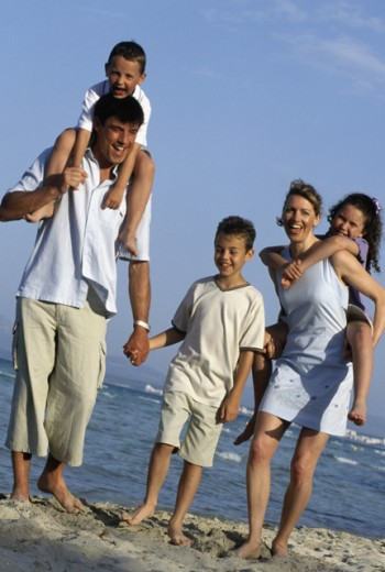 Stock Photo: 1417R-644 Portrait of a mother and father on the beach with their three children