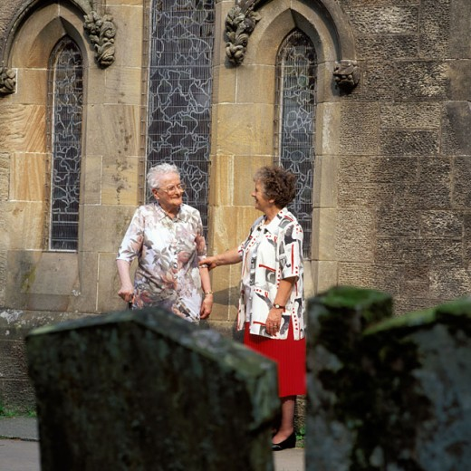 Two senior women standing in a churchyard : Stock Photo