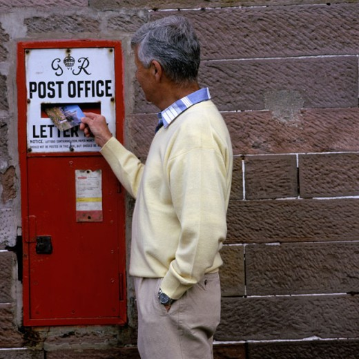 Stock Photo: 1417R-677 Man dropping a postcard in a mailbox