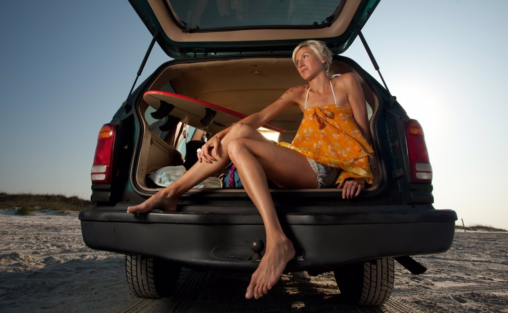 USA, Florida, Woman sitting in back of van on beach : Stock Photo