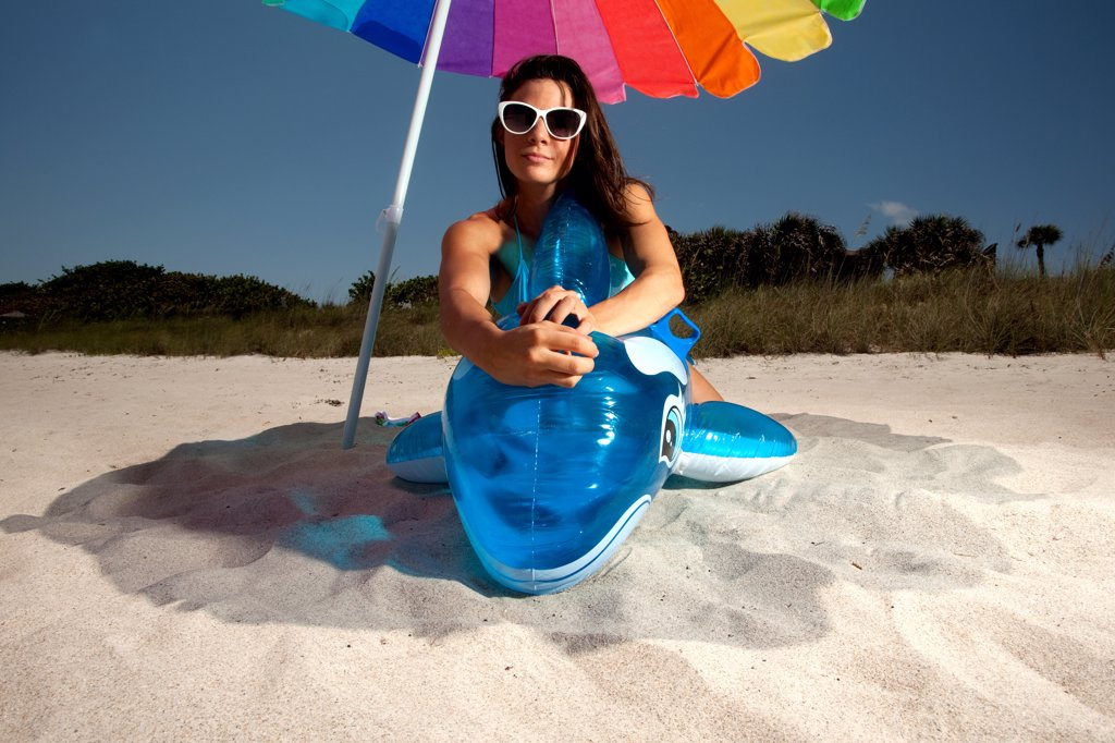 Stock Photo: 1418-1653 USA, Florida, Portrait of young woman playing with Inflatable whale on beach