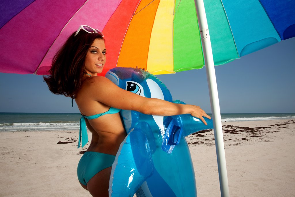 Stock Photo: 1418-1658 USA, Florida, Young woman with Inflatable whale standing under colorful umbrella on beach