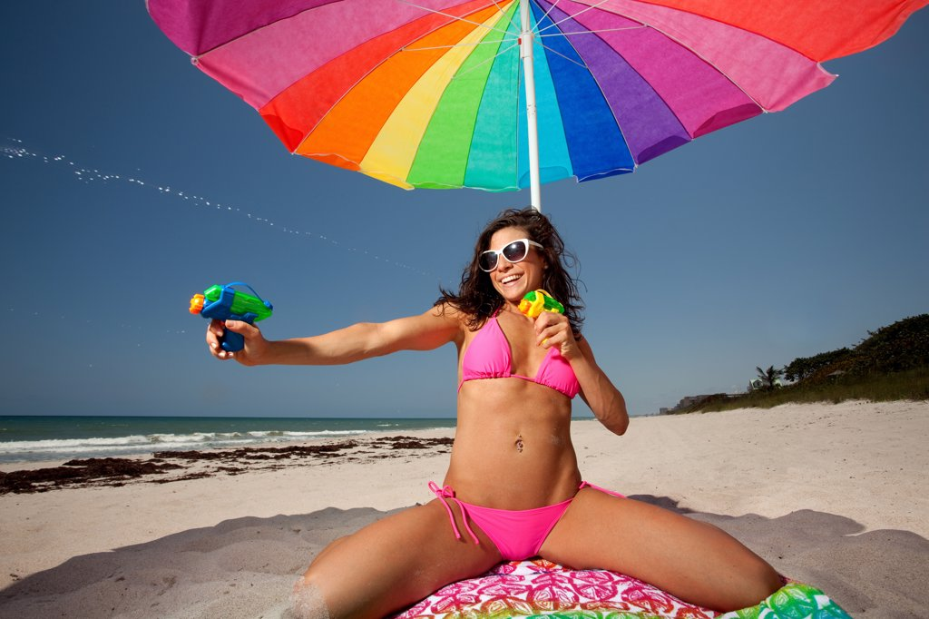 Stock Photo: 1418-1676 USA, Florida, Young woman playing with squirt guns at beach