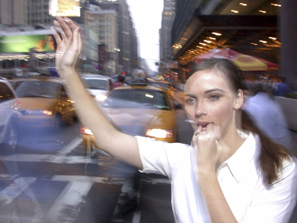 Close-up of a young woman hailing a taxi : Stock Photo