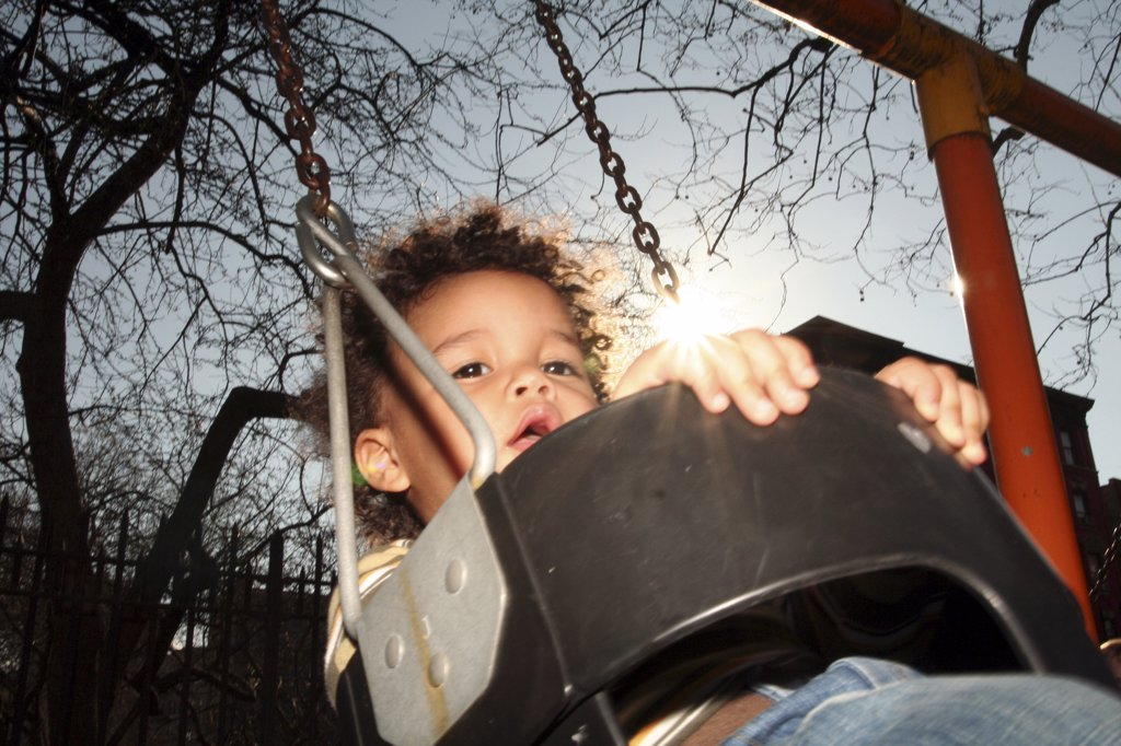 Close-up of a boy swinging on a swing : Stock Photo