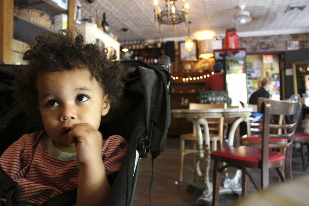 Boy sitting in stroller in a coffee shop : Stock Photo