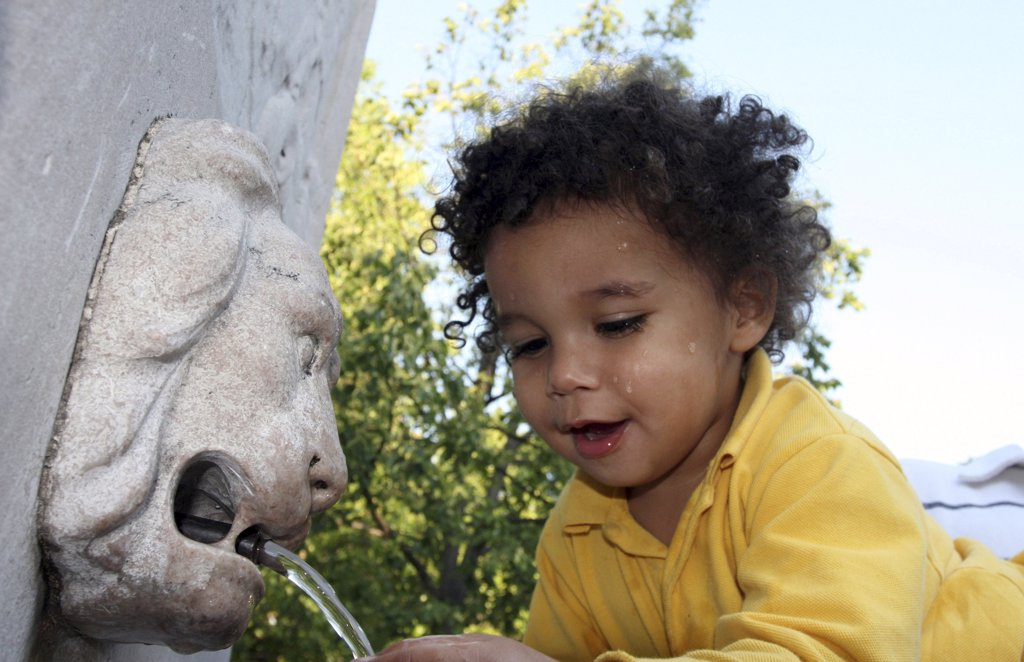Close-up of a boy drinking water from a drinking fountain in a park : Stock Photo